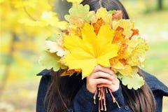 女孩掩藏她的在黄色秋叶后的面孔,花束,秋天 免版税图库摄影