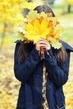 女孩掩藏她的在黄色秋叶后的面孔,花束,秋天 免版税库存图片