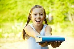 女孩提供一本书 免版税库存照片