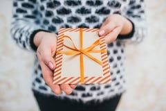 女孩提出一个礼物圣诞节信封 免版税库存图片