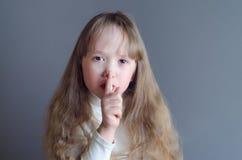 女孩握一个手指对他的嘴 免版税库存照片
