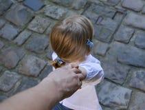 女孩握她的父亲` s手 免版税图库摄影