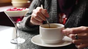 女孩搅动在一个白色杯子的糖 女性递与一杯茶的特写镜头 股票视频