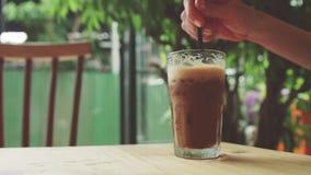 女孩搅动被冰的咖啡并且采取它 免版税库存照片