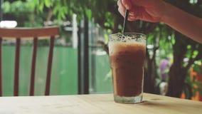 女孩搅动被冰的咖啡并且采取它 免版税库存图片