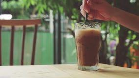 女孩搅动被冰的咖啡并且采取它 股票视频