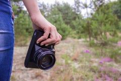 女孩摄影师在森林在她的手上拿着一台老葡萄酒影片照相机 免版税库存照片