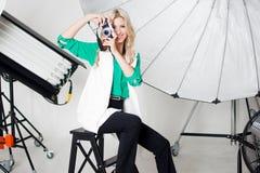 女孩摄影师拍在聚光灯背景的一张照片  图库摄影