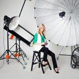 女孩摄影师拍在聚光灯背景的一张照片  免版税库存图片