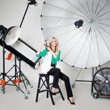 女孩摄影师拍在聚光灯背景的一张照片  免版税图库摄影