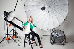 女孩摄影师拍在聚光灯背景的一张照片  免版税库存照片