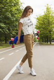 女孩摆在与longboard的时装模特儿在轨道的公园 室外的生活方式 免版税库存照片
