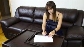 女孩撕开一张纸坐一个皮革沙发 影视素材
