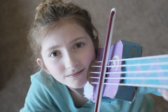 女孩播放玩具小提琴乐趣的和美丽 库存照片