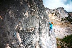 女孩攀登岩石 免版税库存照片