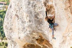 女孩攀登岩石 图库摄影