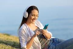 女孩放松的在网上听到音乐户外 库存照片