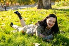 女孩放置年轻人的草绿色 免版税库存图片