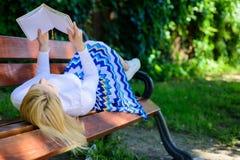 女孩放置放松与书,绿色自然背景的长凳公园 妇女花费与书的休闲 有趣的书 聪明 免版税库存图片
