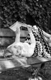 女孩放置放松与书,绿色自然背景的长凳公园 妇女花费与书的休闲 自已的时刻 库存照片