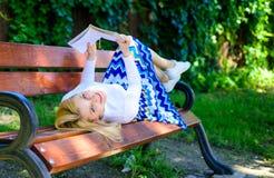 女孩放置放松与书,绿色自然背景的长凳公园 妇女花费与书的休闲 读的女孩户外 图库摄影