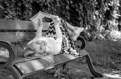 女孩放置放松与书,绿色自然背景的长凳公园 妇女花费与书的休闲 读的女孩户外 库存照片