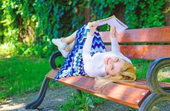 女孩放置放松与书,绿色自然背景的长凳公园 妇女花费与书的休闲 读的女孩户外 免版税图库摄影