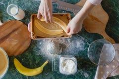 女孩放装填的裁减香蕉入馅饼面团 免版税库存照片