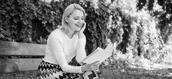 女孩敏锐对书继续读 作为爱好的读书文学 女孩坐放松与书,绿色自然背景的长凳 免版税库存照片
