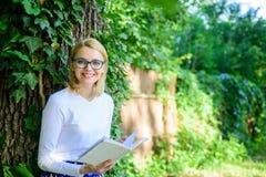女孩敏锐对书继续读 放松在公园阅读书的妇女白肤金发的作为断裂 放松与书绿色的女孩 库存图片