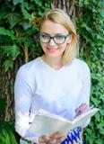 女孩敏锐对书继续读 放松在公园阅读书的妇女白肤金发的作为断裂 放松与的书痴学生 免版税库存照片