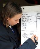 女孩数学题学校解决 库存照片