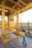 女孩敲响响铃在佛教寺庙 库存图片