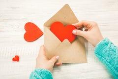 女孩文字情书的手在圣徒情人节 Handma 免版税库存照片