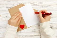女孩文字情书的手在情人节 手工制造明信片 妇女在明信片写为2月14日假日庆祝 库存照片