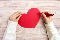 女孩文字情书的手在情人节 手工制造红色心脏明信片 妇女在明信片写为2月14日假日铈 免版税库存图片