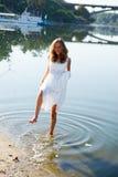 女孩新娘获得在飞溅的水的乐趣在河 免版税库存照片
