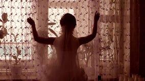 女孩新郎由窗口剪影打开帷幕在屋子里 免版税图库摄影