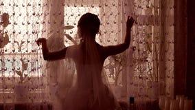 女孩新郎由窗口剪影打开帷幕在屋子里 库存照片