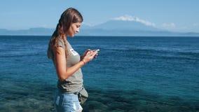 女孩旅客使用电话,类型消息 海洋,在背景,慢动作的山 影视素材