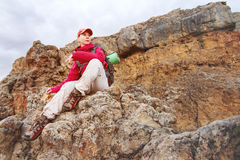 女孩旅客坐一个岩石高在高加索的山反对岩石落日背景和 免版税图库摄影
