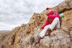 女孩旅客坐一个岩石高在高加索的山反对岩石落日背景和 免版税库存照片