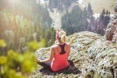女孩旅客坐在瑜伽姿势的一座山顶部 旅行的女孩爱 旅客的概念 看法从 免版税库存照片