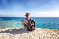 女孩旅客坐岩石并且敬佩蓝色无边的se 免版税库存照片