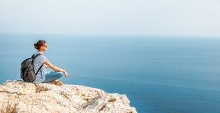 女孩旅客坐岩石并且敬佩蓝色无边的se 库存照片