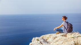 女孩旅客坐岩石并且敬佩蓝色无边的se 库存图片