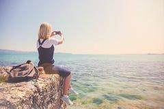 女孩旅客拍在照相机美丽的景色的照片从海 旅行的女孩爱 概念为 免版税图库摄影