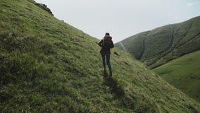 女孩旅客沿在小山顶的山道路去在峭壁在峡谷 股票录像