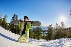 女孩旅游雪板滑雪胜地雪冬天山愉快的微笑的妇女假日极端体育假期 图库摄影