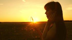 女孩旅行并且听音乐和舞蹈在日落的光芒 r 股票录像